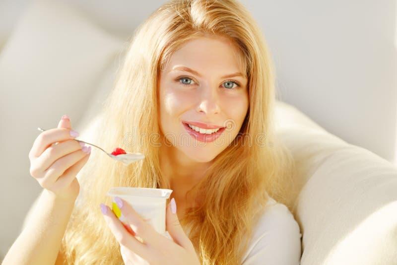 Jonge Vrouw die Yoghurt eet royalty-vrije stock afbeelding