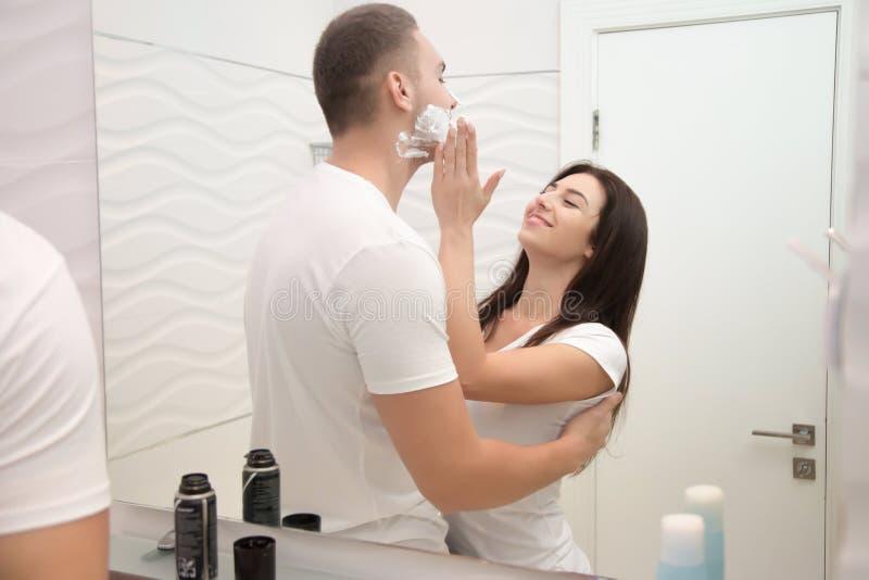 Jonge vrouw die zacht schuim aanvragen een man aan scheerbeurt stock afbeelding
