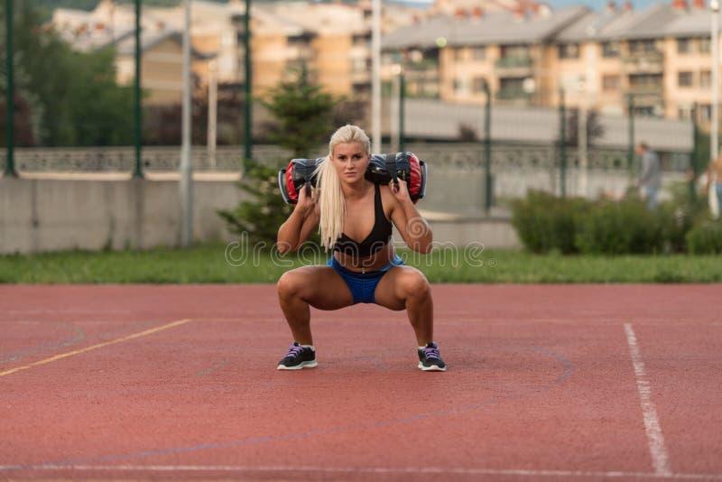 Jonge Vrouw die Zak Hurkende Oefening uitvoeren Openlucht stock afbeelding