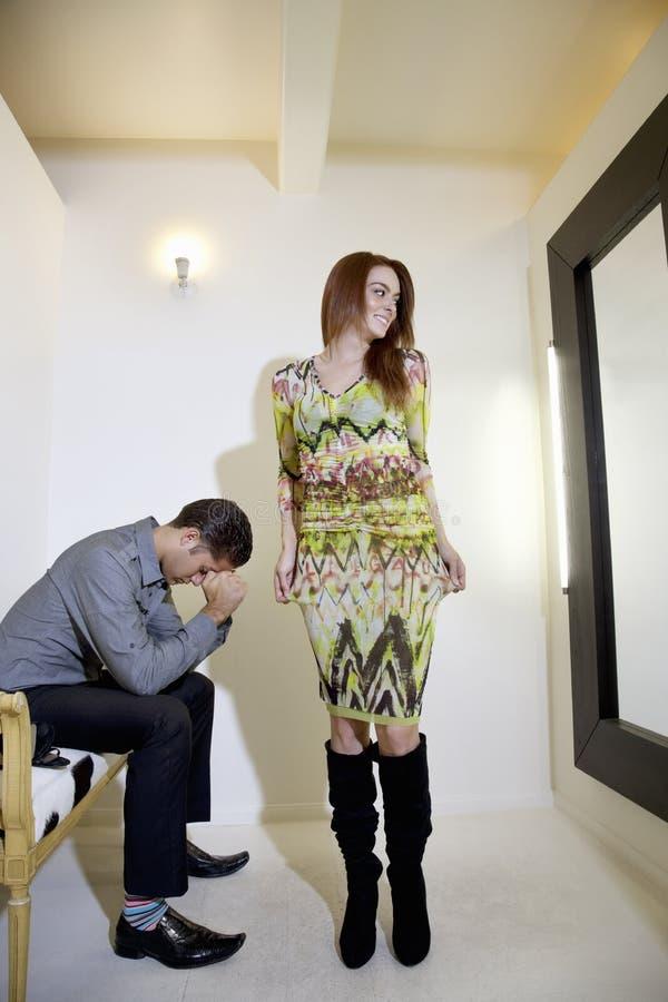 Jonge vrouw die zelf in spiegel bekijkt terwijl man zitting op stoel met handen op gezicht stock afbeeldingen