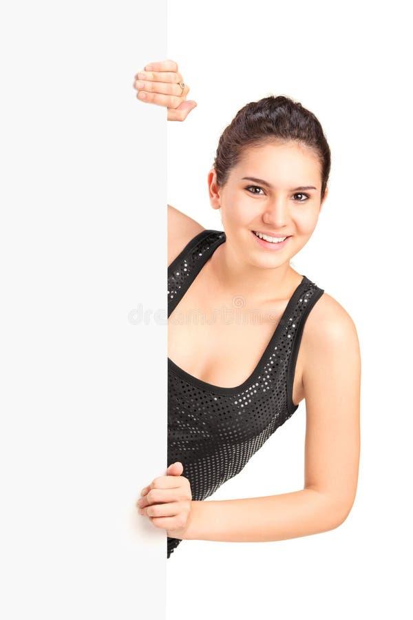 Jonge vrouw die zich achter een leeg paneel bevinden stock afbeelding