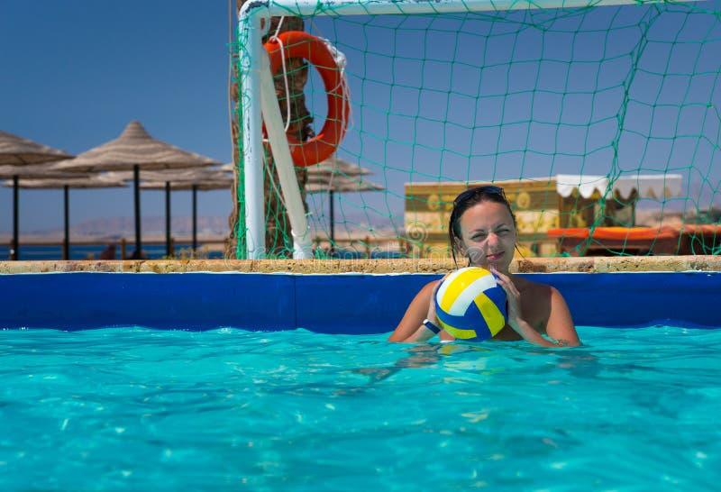 Jonge vrouw die zich bij de poort in polo van het pool het speelwater bevinden royalty-vrije stock fotografie