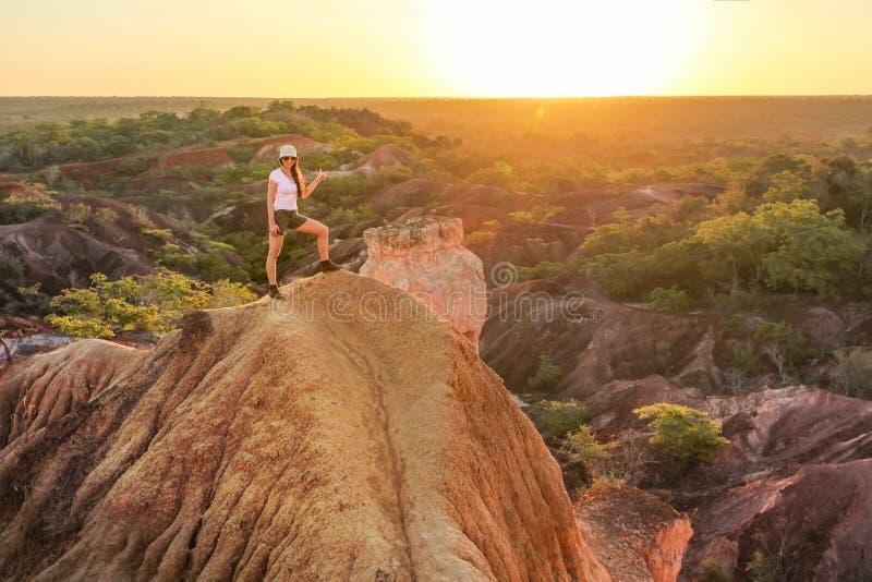 Jonge vrouw die zich bovenop de heuvel bevinden, die op de zon richten stock foto's