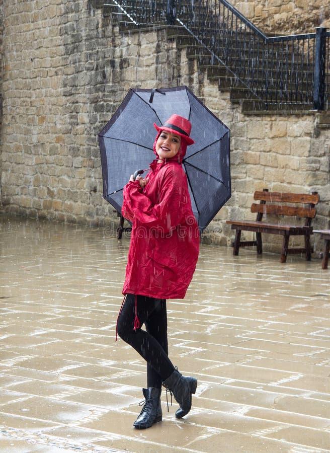 Jonge vrouw die zich in de regen bevinden royalty-vrije stock foto