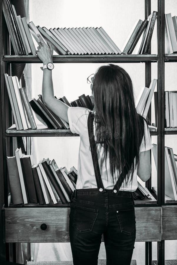 Jonge vrouw die zich dichtbij boekenrekken bevindt en boeken kiest stock foto's