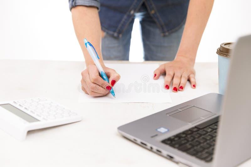 Jonge vrouw die zich dichtbij bureau met laptop bevinden die nota's en planning nemen royalty-vrije stock afbeeldingen