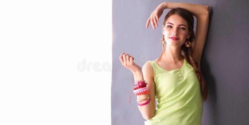 Download Jonge Vrouw Die Zich Dichtbij Donkere Muur Bevinden Stock Afbeelding - Afbeelding bestaande uit armband, meisje: 107705715