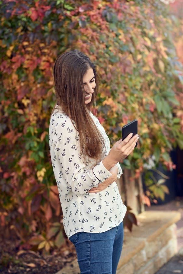 Jonge vrouw die zich in een de herfststraat bevinden die op haar mobiele telefoon texting royalty-vrije stock afbeelding