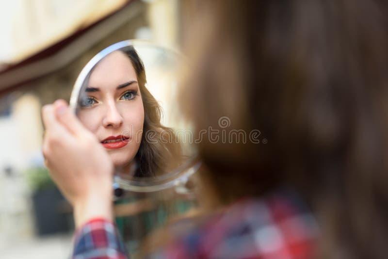 Jonge vrouw die zich in een kleine spiegel bekijken royalty-vrije stock foto's