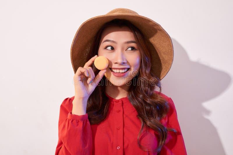 Jonge vrouw die zich met Frans zoet koekje macaron over witte achtergrond bevinden stock foto