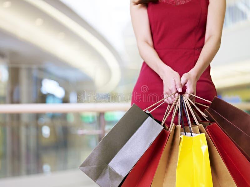 Jonge vrouw die zich met het winkelen zakken in handen bevinden stock afbeeldingen