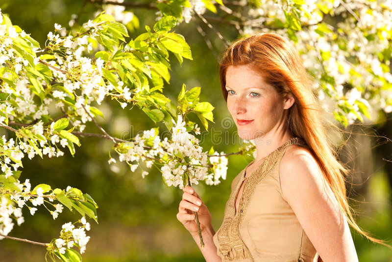 Jonge vrouw die zich onder bloeiende kersenboom bevindt royalty-vrije stock afbeeldingen