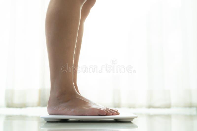 Jonge vrouw die zich op digitale gewichtsschaal bevinden royalty-vrije stock afbeelding