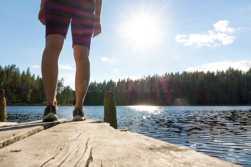Jonge vrouw die zich op een oude houten dok en een pijler bij een meer bevinden stock foto's