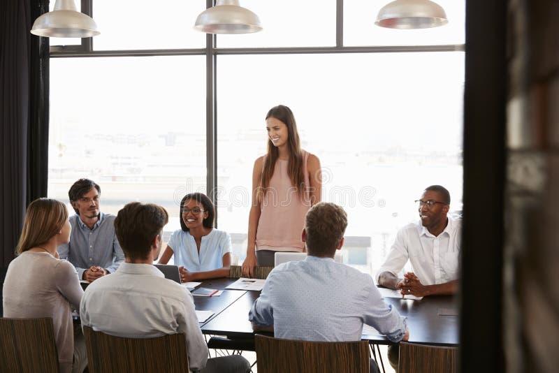 Jonge vrouw die zich op een vergadering in een bedrijfsbestuurskamer bevinden stock afbeelding