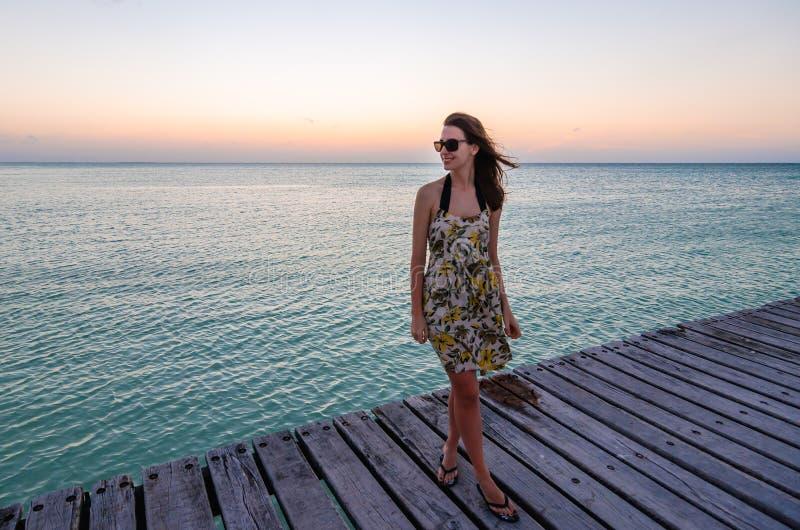 Jonge vrouw die zich op kustpier bij zonsondergang bevinden stock afbeeldingen