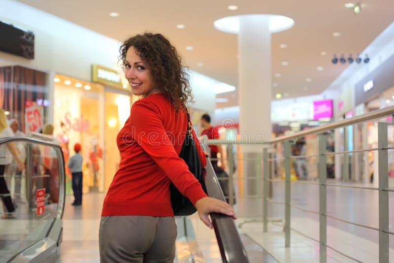 Jonge vrouw die zich op roltrap bevindt royalty-vrije stock foto