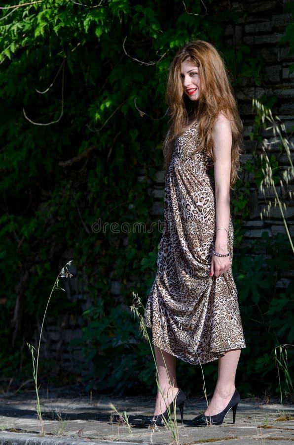 Jonge vrouw die zich tegen rotsenmuur bevinden met lange bladeren royalty-vrije stock foto