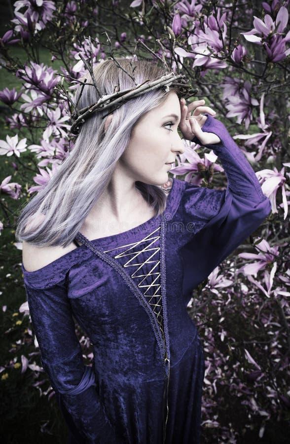 Jonge vrouw die zich voor tot bloei komende boom bevinden royalty-vrije stock afbeelding