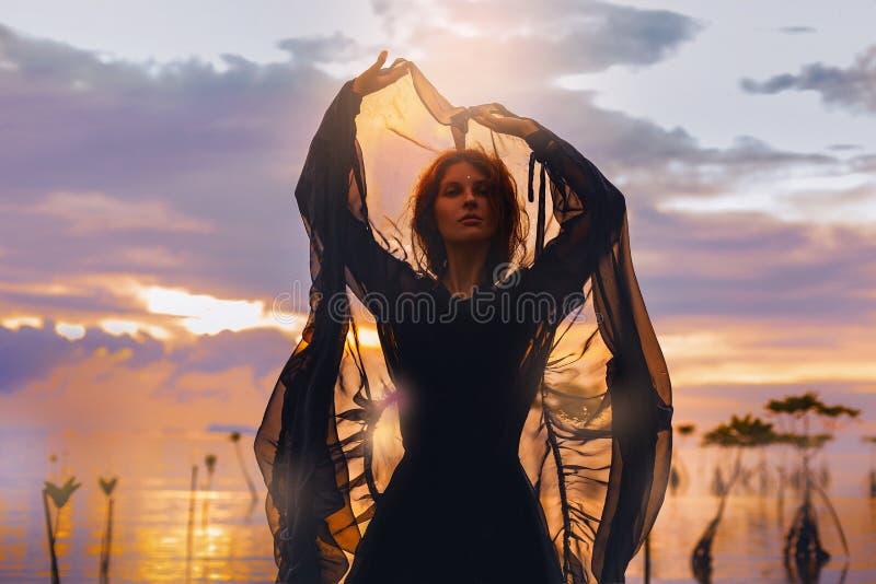 Jonge vrouw die zich in water bij zonsondergangsilhouet bevinden royalty-vrije stock afbeelding