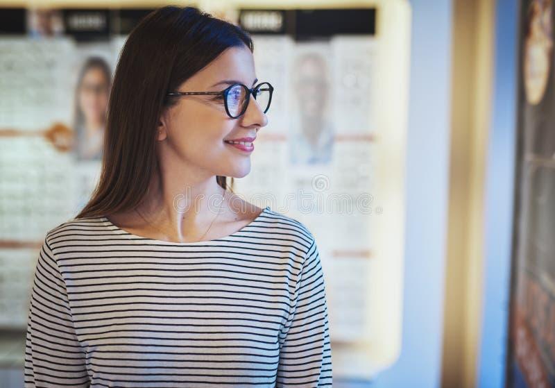 Jonge vrouw die zijdelings in nieuwe oogglazen kijken stock foto
