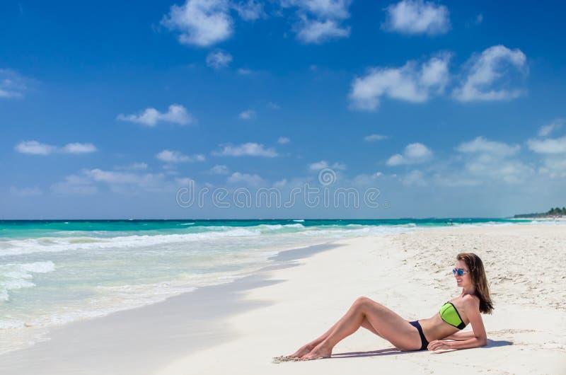 Jonge vrouw die zon krijgen bij tropisch wit zandig strand royalty-vrije stock foto's