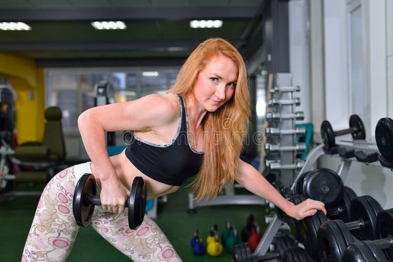 Jonge Vrouw die Zwaargewicht Oefening met Domoren op Breedste Spier opheffen van terug bij Gymnastiek stock foto's