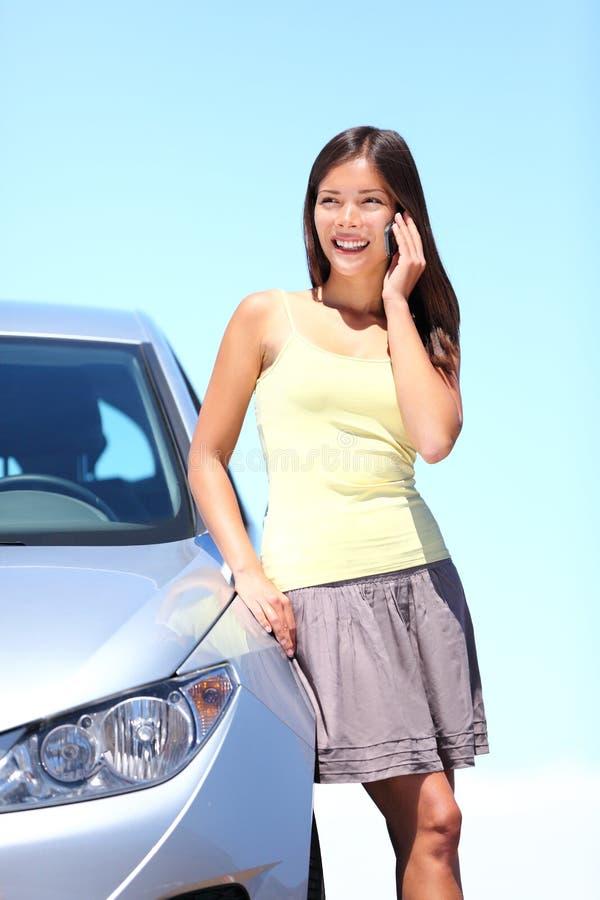Jonge vrouw door auto op mobiele telefoon royalty-vrije stock fotografie