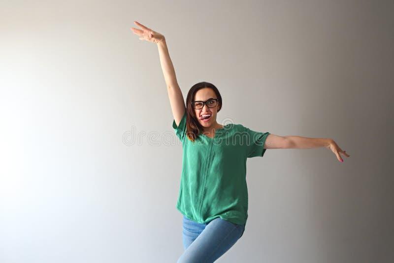 Jonge vrouw door de grijze muur die bij de camera glimlachen stock afbeeldingen