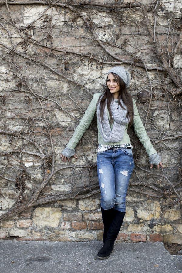 Jonge vrouw door de muur bij de herfst royalty-vrije stock afbeelding