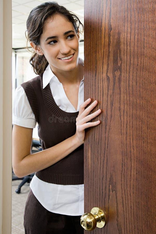 Jonge vrouw door deur royalty-vrije stock afbeeldingen