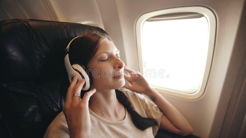 Jonge vrouw in draadloze hoofdtelefoons die aan muziek luisteren en tijdens vlieg in vliegtuig glimlachen royalty-vrije stock afbeelding