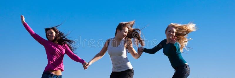 Jonge vrouw drie die in het gebied springt royalty-vrije stock afbeelding