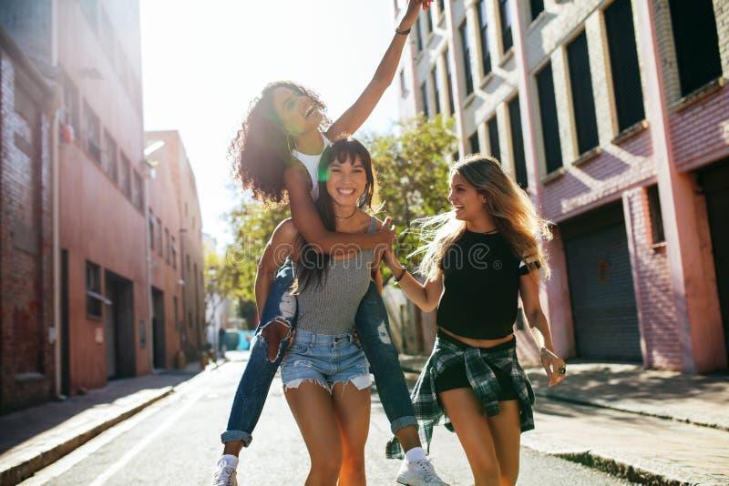Jonge vrouw drie die pret op stadsstraat hebben royalty-vrije stock foto