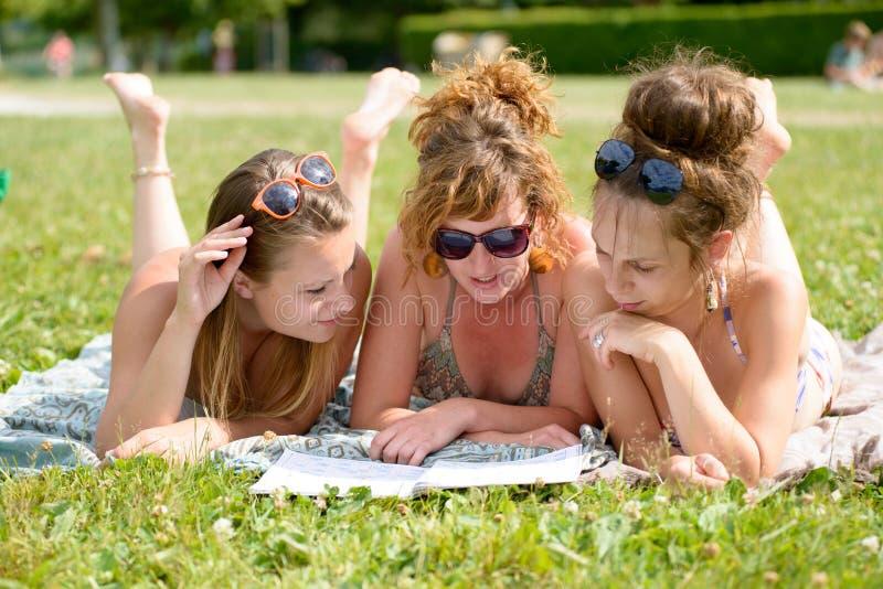 Jonge vrouw drie op het strand die een tijdschrift lezen stock fotografie