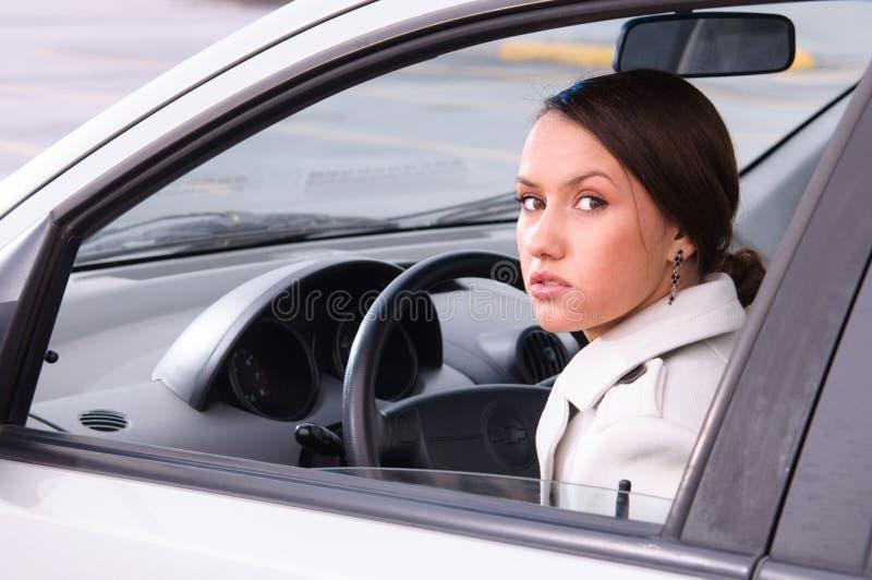 Jonge vrouw in een auto stock foto