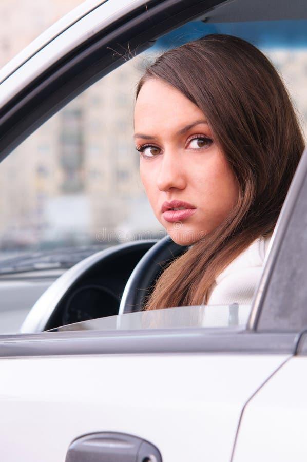 Jonge vrouw in een auto stock afbeelding