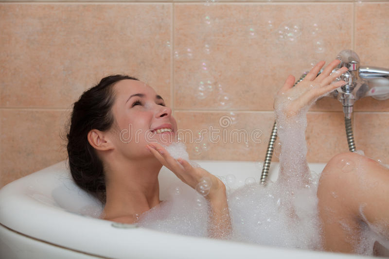 Jonge vrouw in een badkamers. stock foto