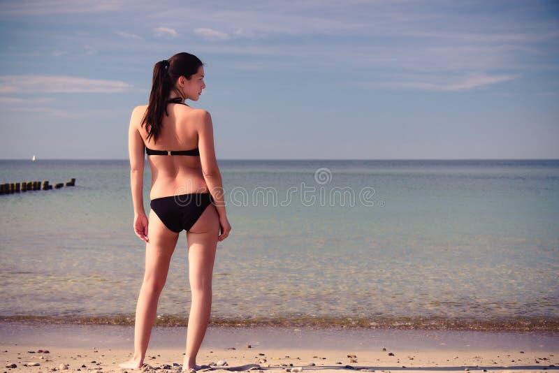 Jonge vrouw in een bikini op het strand royalty-vrije stock afbeelding