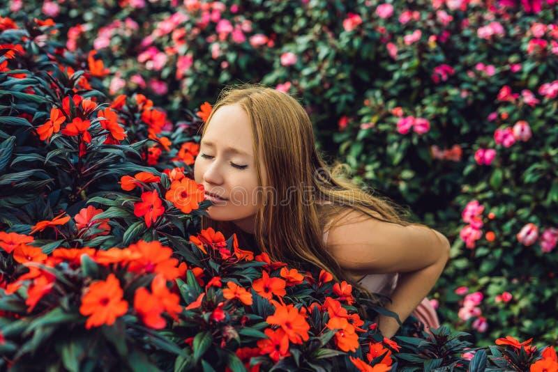 Jonge vrouw in een bloemserre Heldere tropische bloemen stock foto