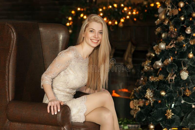 Jonge vrouw in een comfortabel binnenland van Kerstmis Het meisje zit onder een Kerstboom onder vele giften Het voorbereidingen t stock foto's