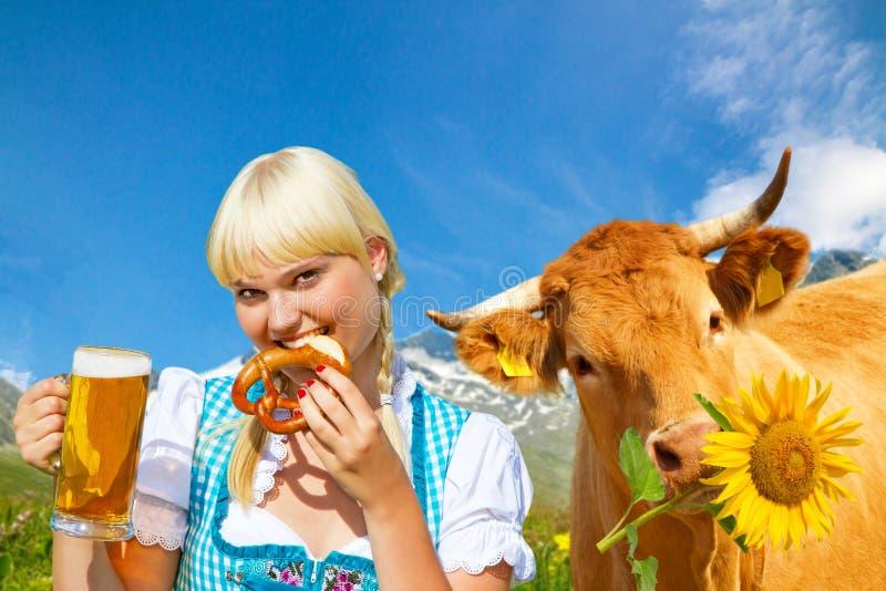 Jonge vrouw in een dirndl met gelukkige koe royalty-vrije stock fotografie