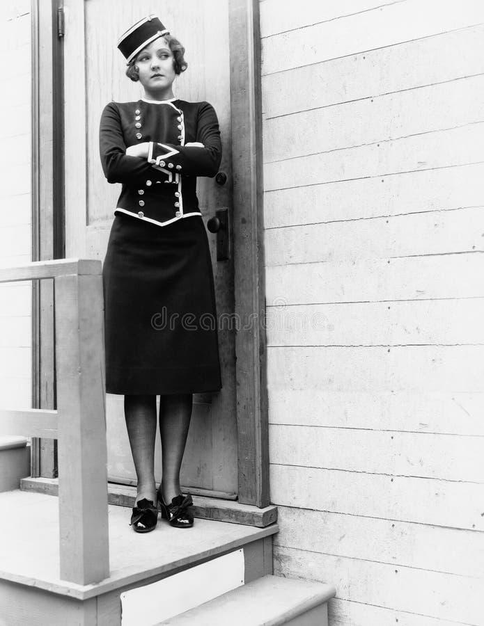 Jonge vrouw in een eenvormige status met haar die wapens voor een gesloten deur worden gekruist (Alle afgeschilderde personen zij royalty-vrije stock fotografie
