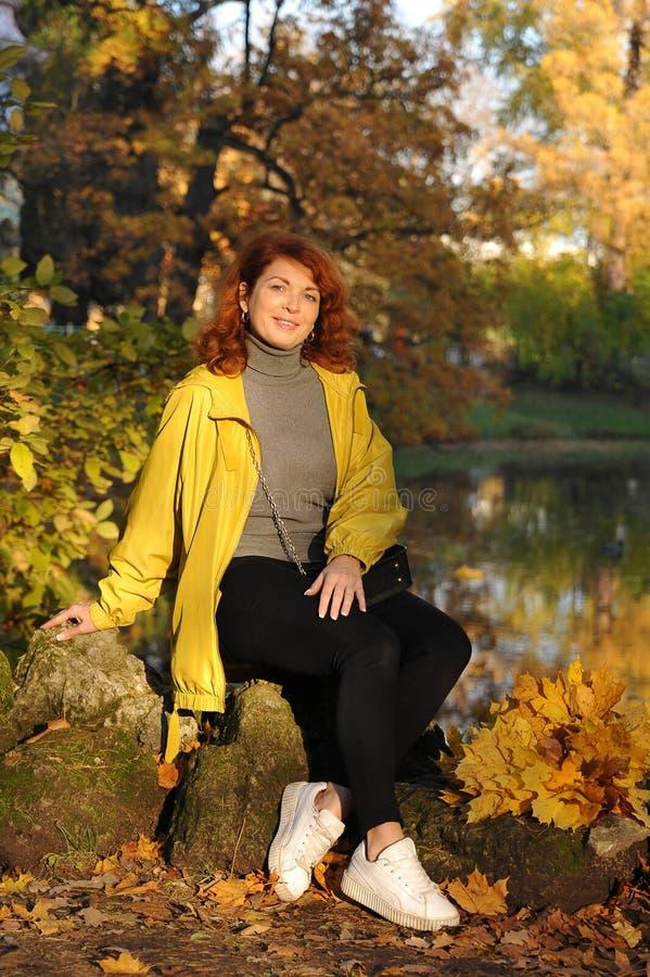 Jonge vrouw in een geel jasje stock foto's
