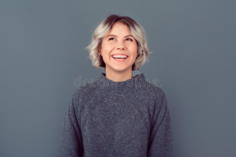 Jonge vrouw in een grijs die beeld van de sweaterstudio op grijze achtergrond wordt geïsoleerd die omhoog eruit zien royalty-vrije stock fotografie