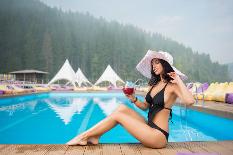 Jonge vrouw in een hoed en een zwarte bikinizitting naast zwembad en het drinken cocktail op de achtergrond van bos stock fotografie