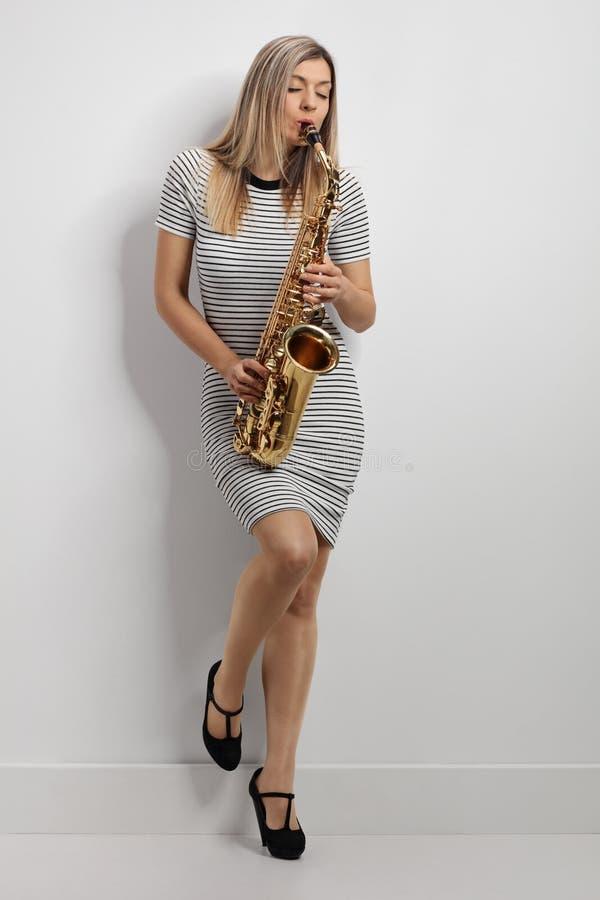 Jonge vrouw in een kleding die een saxofoon spelen royalty-vrije stock foto's