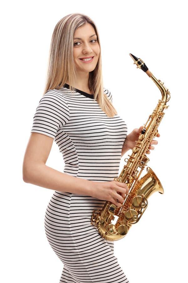 Jonge vrouw in een kleding met een saxofoon stock foto