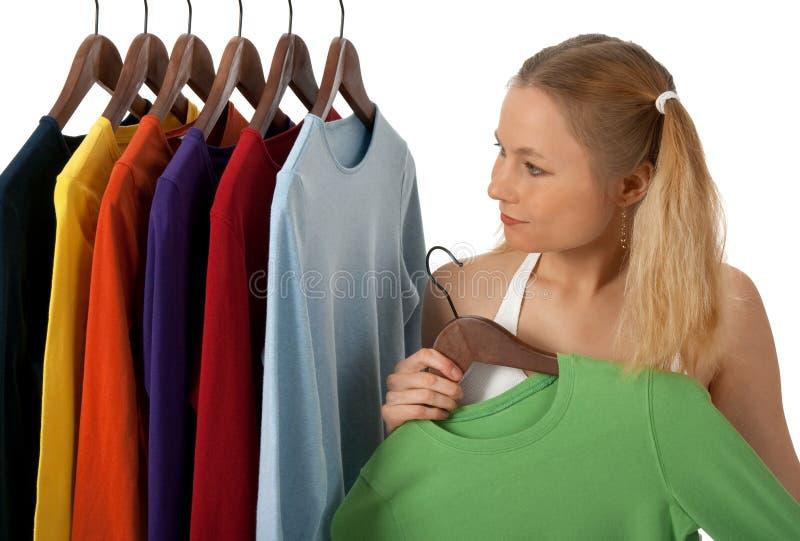 Jonge vrouw in een kledingsopslag stock fotografie