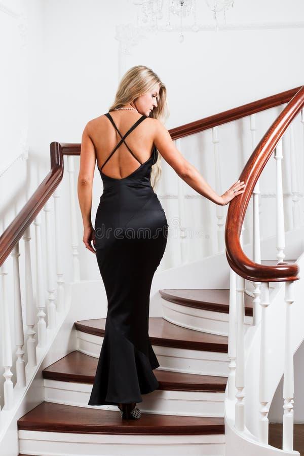 Jonge vrouw in een lange zwarte kleding stock fotografie
